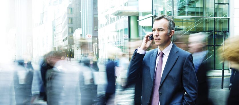 Image of businessman using phone in a busy city